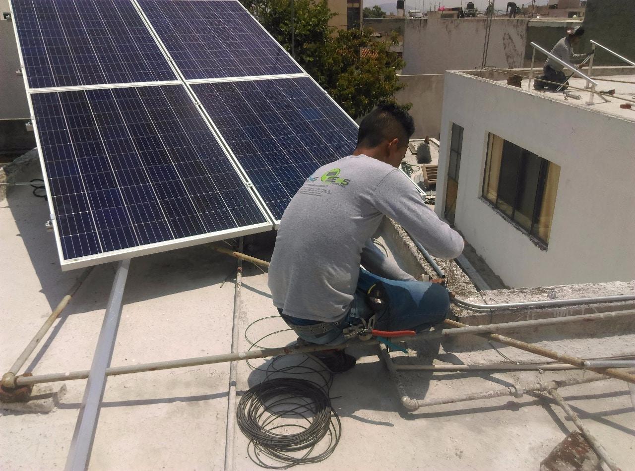 Persona en azotea instalando un panel solar